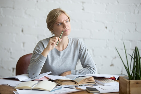 Portrait of a student woman sitting at the desk, frowned, looking aside lifestyle. Education concept photo.