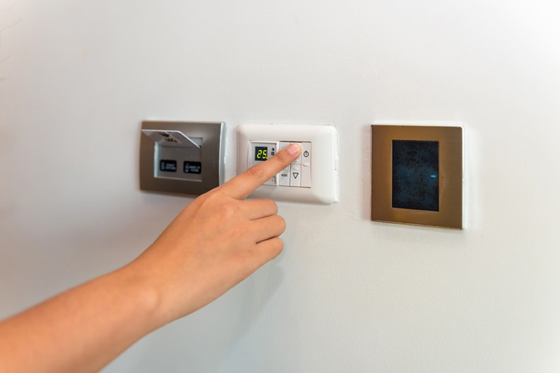 Person changing the temperature on a thermostat, Heat Pump Versus Furnace