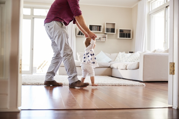Father helping daughter learn to walk at home, side view.